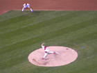 Adam Wainwright pitches as Scott Rolen stands on the edge of the infield grass