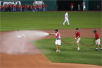 The grounds crew preps the infield after the rain delay
